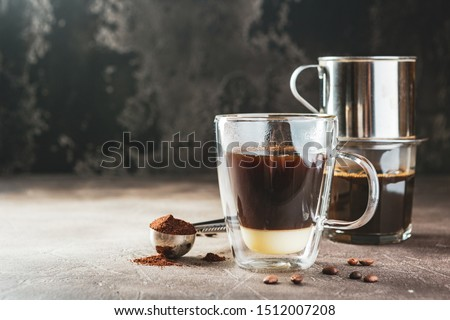 Vietnamese coffee with condensed milk in glass cups and traditional metal coffee maker phin. Traditional method of making of vietnamese coffee. Space for text.