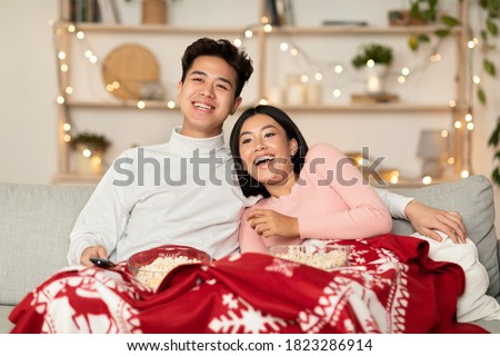 Vietnamese Couple Watching TV On Christmas Evening Enjoying Movies And Popcorn Sitting On Sofa At Home. Japanese Family Covered With Blanket Watches Xmas Television Shows During New Year Holidays