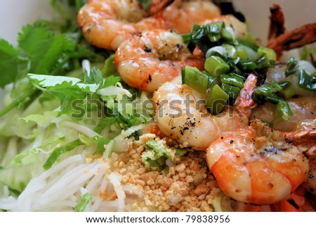 Vietnamese cuisine grilled shrimp on bed of rice noodles and greens, topped with seasoned onions.