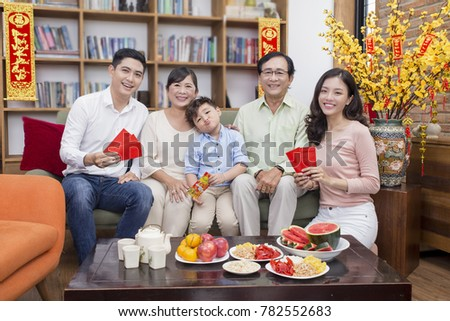 "Vietnamese family celebrate lunar new year and a hanging with the meaning ""Things go smoothly as wish"" and""Wish you happiness and prosperity"" #782552683"