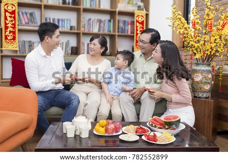 "Vietnamese family celebrate lunar new year and a hanging with the meaning ""Things go smoothly as wish"" and""Wish you happiness and prosperity"" #782552899"