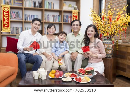 "Vietnamese family celebrate lunar new year and a hanging with the meaning ""Things go smoothly as wish"" and""Wish you happiness and prosperity"" #782553118"