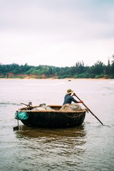 Vietnamese Fisherman heading out in the ocean on his vintage old boat