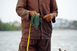 vietnamese fisherman on small boat fishing with fishnet
