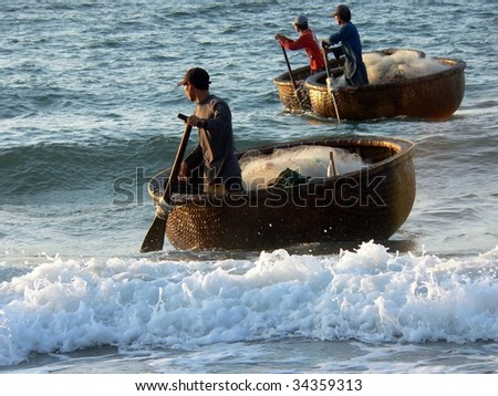 Vietnamese fishermen coming ashore in their coracles after a night's fishing, Mui Ne, Vietnam. Image by Kevin Hellon