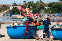 Vietnamese fishermen sort out nets with caught fish to sell in the fish market
