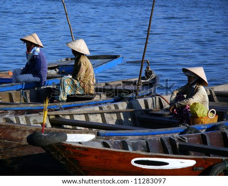 Vietnamese Fishermen waiting to go fishing by the Mekong River, Vietnam. - stock photo