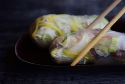 Vietnamese fresh Goi cuon Xoai, filled with fresh vegetables and wrapped in rice paper, served on a plate against a dark background and held by bamboo chopsticks