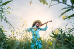 Vietnamese girl playing music from the violin in the middle of a vast meadow.
