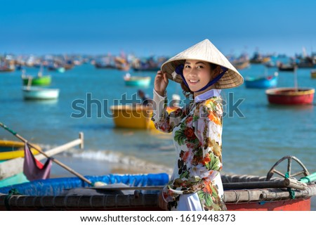 Vietnamese lady with Ao Dai Vietnam traditional dress and conical hat wait at the harbor, Fishing Harbour Mui Ne Vietnam