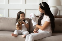 Vietnamese loving mother and toddler daughter wearing crowns casual clothes sit on couch playing with hedgehog and hare animal hand puppet toys. Educational games, having fun with kid at home concept