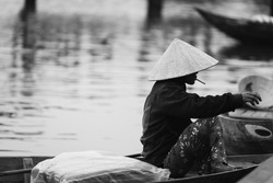 Vietnamese man smoking and waiting for tourist at riverfront of Hoi An old town, Vietnam. Black and White tone.