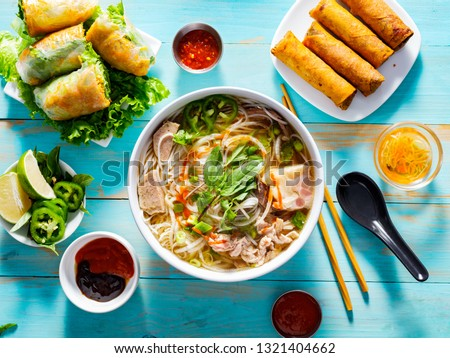 vietnamese pho bo soup with appetizers on table and drizzled with sriracha sauce