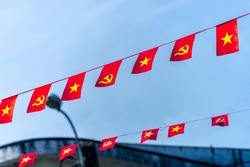 Vietnamese red with yellow star flag and Communist Party of Vietnam flag. Waving colorful national Vietnamese flag in blue sky. Politics and tourism concept