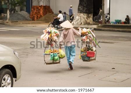 Vietnamese street vendor in Ho Chi Minh City (Saigon) carrying their goods across a street