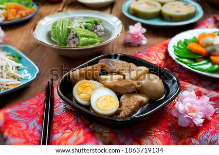 Vietnamese table food for Tet, traditional food on lunar new year: pork belly with hard-boiled eggs braised in coconut water, mixed pickles, rice and other Tet foods on background