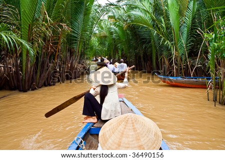 Vietnamese woman rowing a boat in Mekong River in Vietnam - stock photo