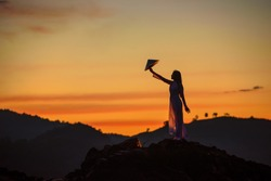 Vietnamese woman stand alone show Vietnam hat in her hand at twilight time
