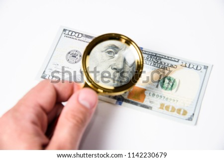 View a hundred dollar bill through a magnifying glass. Authentication of banknotes