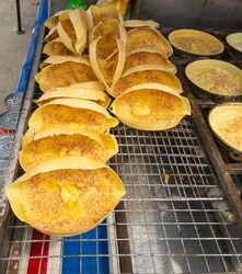 View a row of traditional food called Apam Balik.It is a sweet Malaysian peanut pancake turnover stuffed with a sugary,buttery peanut filling and corn.