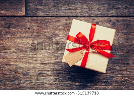View above brown gift box and red ribbon with tag on wood background with space. #515139718