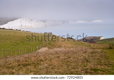View across cliff top towards white cliffs in distance with sea in middle ground