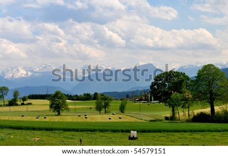 View across green meadows to the glaciers of the mountains around Lake Lucerne in Switzerland