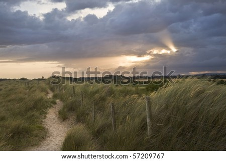 View across sand dunes to countryside with sunbeams through stormy clouds
