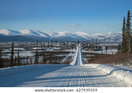 view along dalton highway toward brooks range in north alaska in winter, with oil pipeline seen to right #627939359