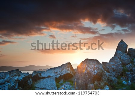 View along West coast of Wales towards beautiful sunset with sunbeams and stunning clouds formations - stock photo