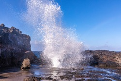 View at a stream of water and steam exploding from Nakalee blowhole, Maui, Hawaii