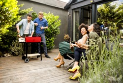 View at happy friends grilling food and enjoying barbecue party outdoors