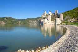 View at restored medieval Golubac fortress, fort Golubac on the bank of the Danube in Serbia across from Romania, major tourist destination. Copy space, text space, background, reflection.