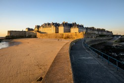 View at sunset of the walled old city of Saint-Malo in Brittany, France, with granite buildings bathed in warm light sticking out above the wall and the Mole beach at the foot of the rampart.