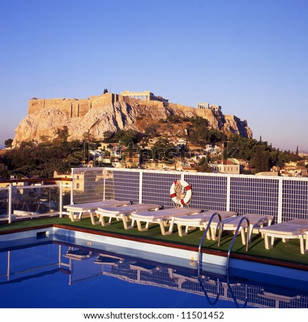 View at the Acropolis in Athens, Greece. At foreground a swimming pool at the roof of a building