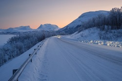 View at the road toward Abisko village in the northen part of Sweden. Car drives on the winter road during sunset. Landscape of arctic circle area in winter.
