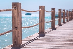 View at the sea from the wooden pier with posts and ropes with sparkling sea water