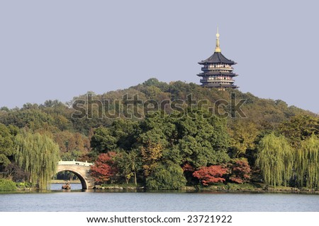 View at the West Lake near Hangzhou in China with bridge and small tourist boatand trees with red leafs