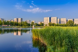 View at Tysiaclecie district in Katowice on a beautiful, sunny day, seen through the pond. Apartment buildings situated neat the lake against blue sky.