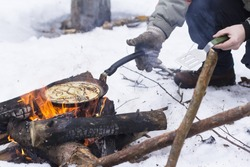 view background people bake pancakes on a fire in the open air in the winter on a holiday Maslenitsa
