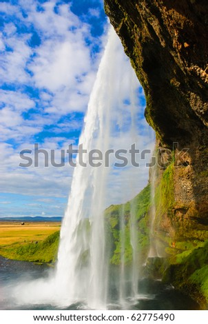 view behind the waterfall Seljalandsfoss in Iceland