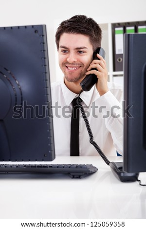 View between two computer monitors of a smiling handsome young stock broker talking on a phone