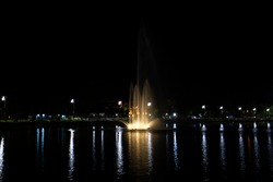 View cityscape Udonthani city and landscape fountain spray in pond night time for thai people travel visit and rest relax at Nong Prajak Recreation Centre Public Park in Udon Thani, Thailand