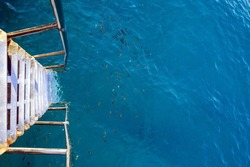 view down from the steel old stairs on the pier into the Mediterranean turquoise blue beautiful sea with fishes. Tropical vacation on the Turkish coast. Copy space.