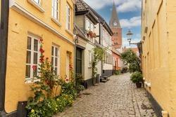 View down the cobblestone street of Hjelmerstald (Hjelmer stable), the historic preserved neighborhood of Aalborg, Denmark