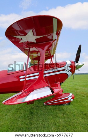 View down the wings of an old red biplane.