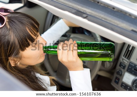 View down through the sunroof of a middle-aged woman drinking alcohol from the bottle while driving a car