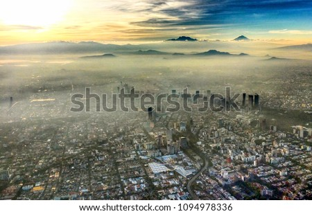 View flying over Mexico City in the morning with the buildings and mountains popping out of the fog and smog.