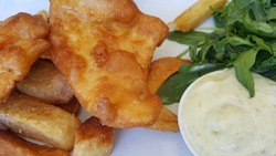 View fof the crispy beer battered fish and chips and green salad vegetable with tar tar sauce. It is a hot dish consisting of fried fish in batter, served with chips originated in England