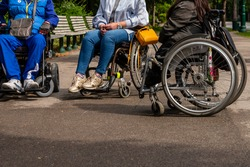 View for two women and one man legs sitting in the wheelchairs. Three people with wheelchairs relaxing in park at sunny day.
